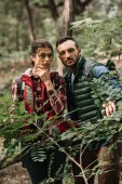 Photo portrait of couple of young travelers with backpacks hiking in woods