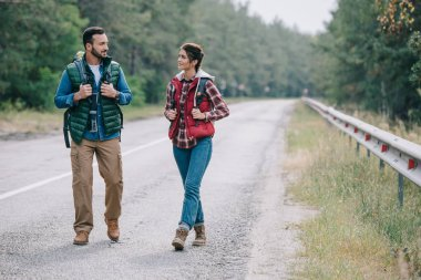 couple of travelers with backpacks walking on road