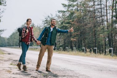 couple of travelers with backpacks holding hands while hitchhiking on road