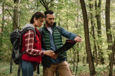 man and woman looking for destination on map while hiking in forest together