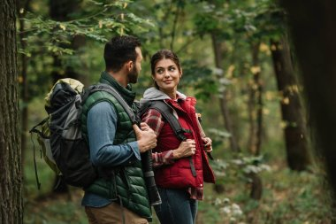 side view of man and woman with backpacks hiking in woods