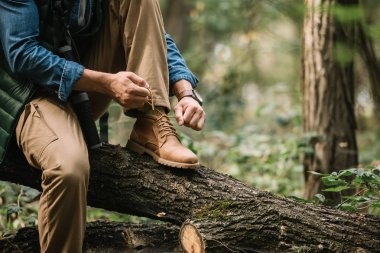 partial view of man tying shoelaces on log while hiking in forest alone