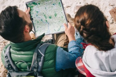 partial view of hikers with map sitting on rocks on sandy beach