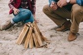 Fotografie couple making campfire on sandy beach