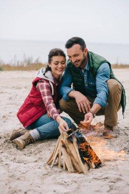 couple roasting marshmallow on campfire on sandy beach