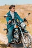 Fotografie pohledný elegantní mladý muž sedí na vinobraní motocyklu na venkově louka