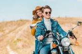 mladý usmívající se pár sedí na retro motorka na venkově louka