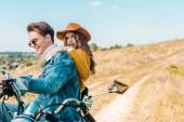 přítelkyně při pohledu na kameru, zatímco přítel sedí na vinobraní motocyklu na venkově louka