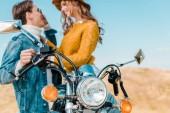 Fotografie selective focus of smiling couple sitting on vintage motorbike