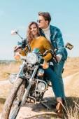 Fotografie smiling girlfriend sitting on motorbike while boyfriend looking away on meadow