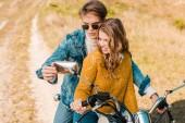 Fotografie beautiful couple looking at mirror of retro motorbike