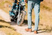 Fotografie oříznutý pohled člověka chůzi po stezce poblíž retro motorka