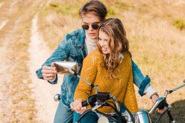 Beautiful couple looking at mirror of retro motorbike stock vector