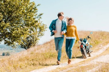 happy couple running on rural meadow with motorbike on background