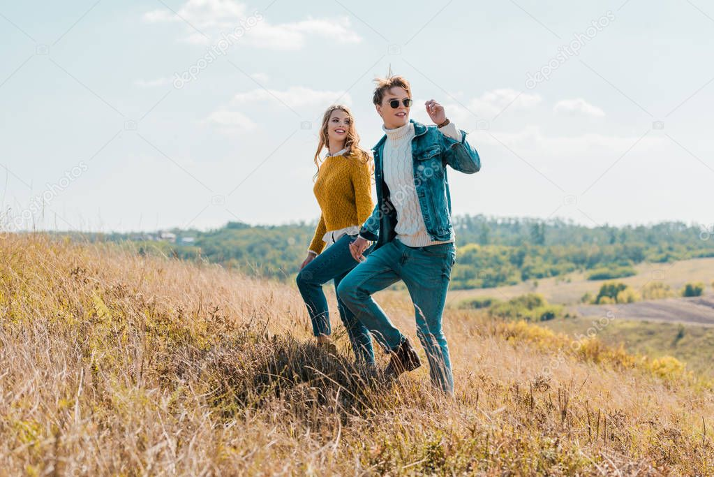 attractive couple walking on rural meadow