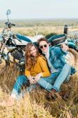 Fotografie usmívající se pár sedící poblíž retro motorka
