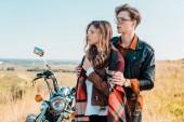 Fotografie pár v brýlích odvrátila a stojící poblíž retro motorka