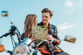 Fotografie young couple of travelers holding map and sitting on motorbike against blue sky