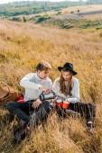 Fotografie mladý pár nalil čaj z termosky na venkově louka