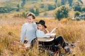 Fotografie usmívající se holka drží kytaru zatímco koukal