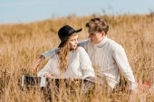 Photo attractive young couple looking at each other on meadow
