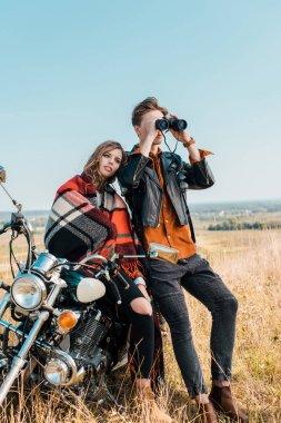 Young boyfriend looking through binoculars near girlfriend sitting on motorbike stock vector