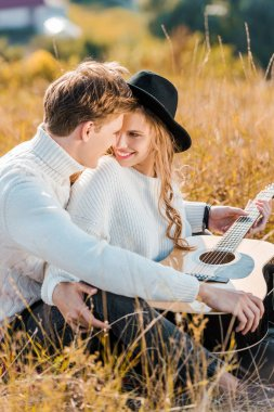 smiling couple looking at each other while young man holding guitar