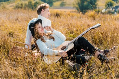 happy young couple with guitar relaxing on meadow