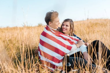 happy couple with american flag resting on grass, independence day concept