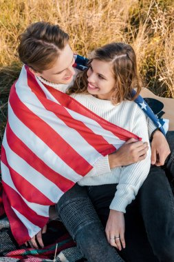 smiling couple with american flag at picnic, independence day concept