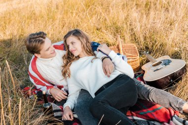 young lovers with american flag resting on rural meadow, independence day concept