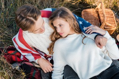 young couple with american flag resting on rural meadow, independence day concept