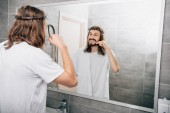 zadní pohled na Ježíše s ručníkem přes rameno čištění zubů v koupelně