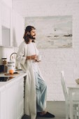 Fotografie side view of happy Jesus in crown of thorns standing with cup of coffee in kitchen at home