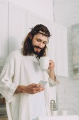 selective focus of Jesus in crown of thorns standing with cup of coffee and using smartphone in kitchen at home