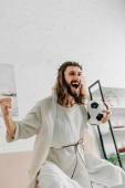 excited Jesus in crown of thorns  gesturing by hands and watching football match at home