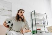 Fotografie emocionální Ježíše v trnová koruna sedí na pohovce s fotbalovým míčem a sledují fotbalový zápas doma