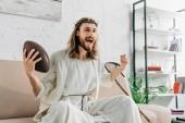 Fotografie nadšený Ježíše v trnová koruna, pokynul rukou a americký fotbal na gauči doma