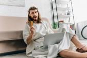 Fotografie glücklich Jesus zeigen, Kreditkarte, zwinkert und Online-Einkäufen auf Laptop in der Nähe von Sofa zu Hause