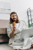 Fotografie fröhlich Jesus zeigen, Kreditkarte, zwinkert und Online-Einkäufen auf Laptop in der Nähe von Sofa zu Hause
