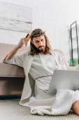 Fotografie nachdenklich Jesus sitzen auf Boden mit Kreditkarte und Online-shopping auf Laptop in der Nähe von Sofa zu Hause zu tun