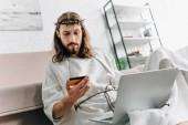 Fotografie nachdenklich Jesus betrachten Kreditkarte und Online-Einkäufen auf Laptop in der Nähe von Sofa zu Hause