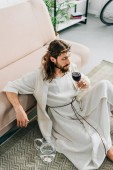 Fotografie high angle view of Jesus in crowns of thorns and robe sitting on floor near jug of water and drinking wine from glass at home