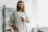 Fotografie portrét šťastný Ježíše v trnová koruna při pohledu na fotoaparát a držení digitální tabletu doma