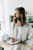 Fotografie pensive Jesus in crown of thorns and robe holding textbook and looking away in modern office