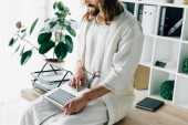 Photo partial view of Jesus sitting on table and working on laptop in modern office