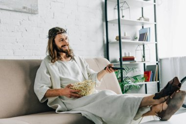 happy Jesus in crown of thorns watching tv and sitting with bowl of popcorn on sofa at home