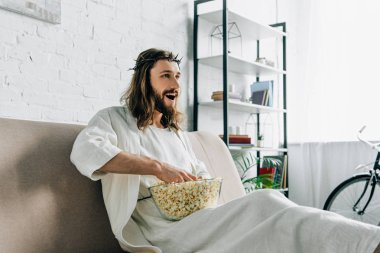 Cheerful Jesus in crown of thorns watching tv and sitting with bowl of popcorn on sofa at home stock vector