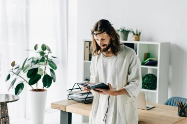 smiling Jesus in crown of thorns and robe reading textbook near working table in modern office