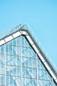 low angle view of glass building and roof against blue sky